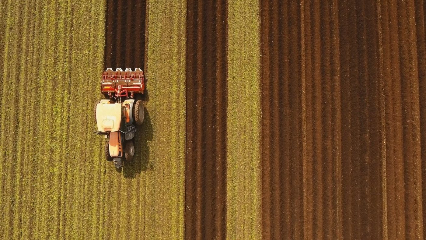 Farmer In Tractor Preparing Land With Seedbed Cultivator In Farm